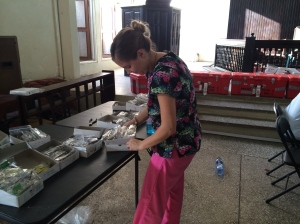 Pam works hard sorting reading glasses for the hundreds that need them.